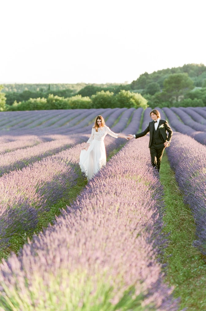 Bride and Groom walking hand in hand through a blooming lavender field in the Luberon in Provence