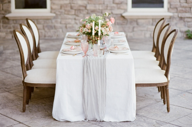 Sideview of a luxurious wedding reception table filled with centerpieces of roses