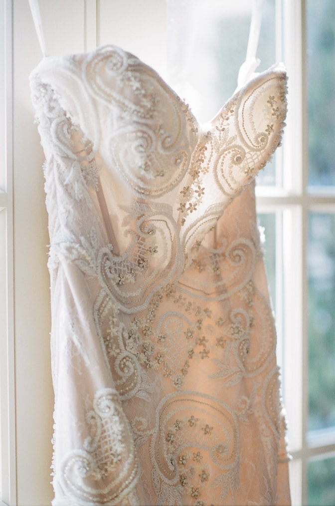 Luxurious Galia Lahav Wedding Gown hanging on the window at Castle Cliff Estate