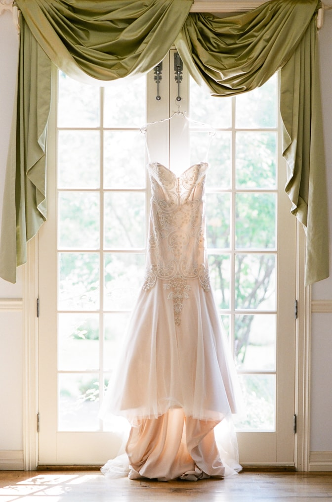 Wedding dress hanging on the window at Castle Cliff Estate