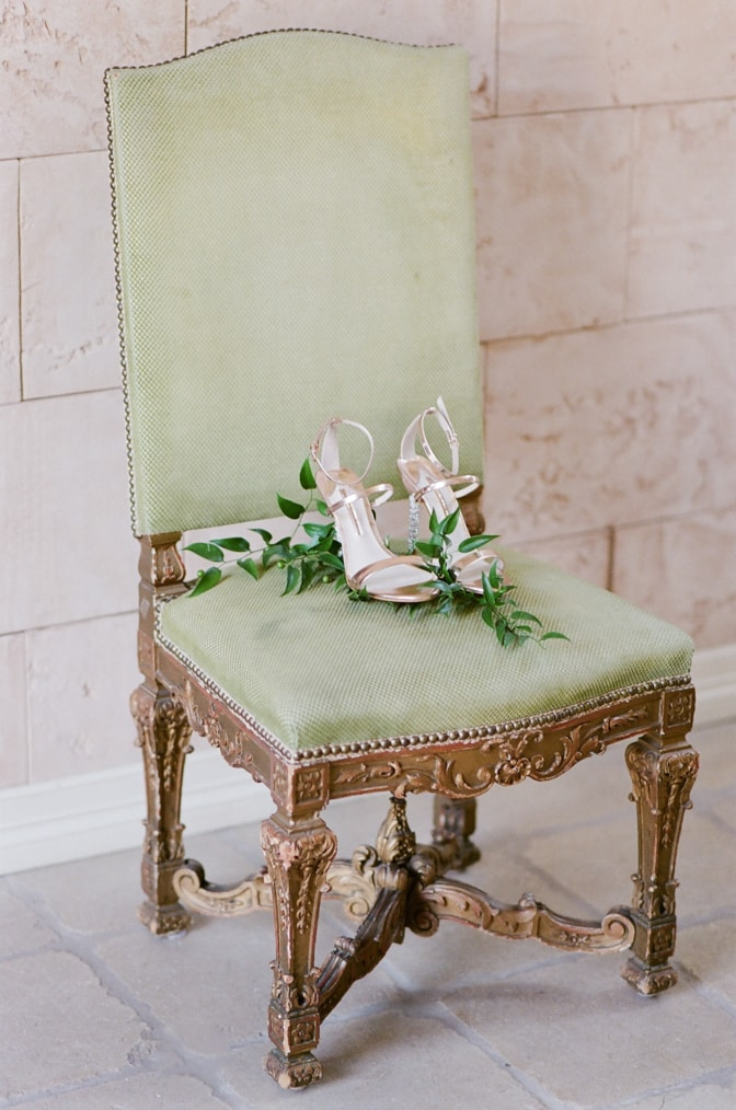 Luxuriou wedding shoes on top of a classic chateau chair