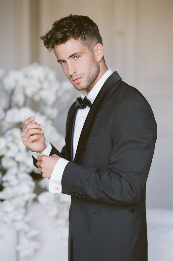 a style guide for the modern groom showing a groom in his black tux