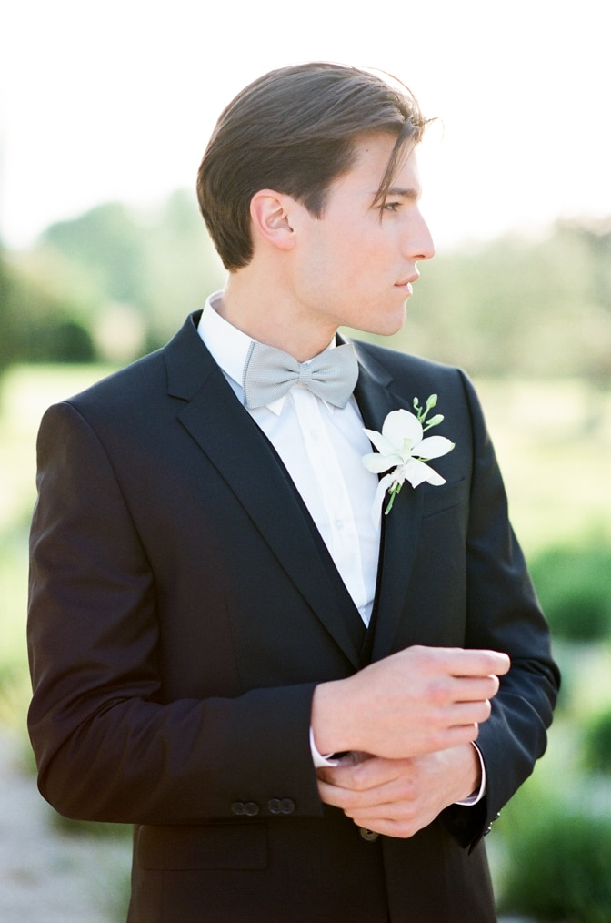 A style guide for the modern groom showing a groom with his blue bowtie