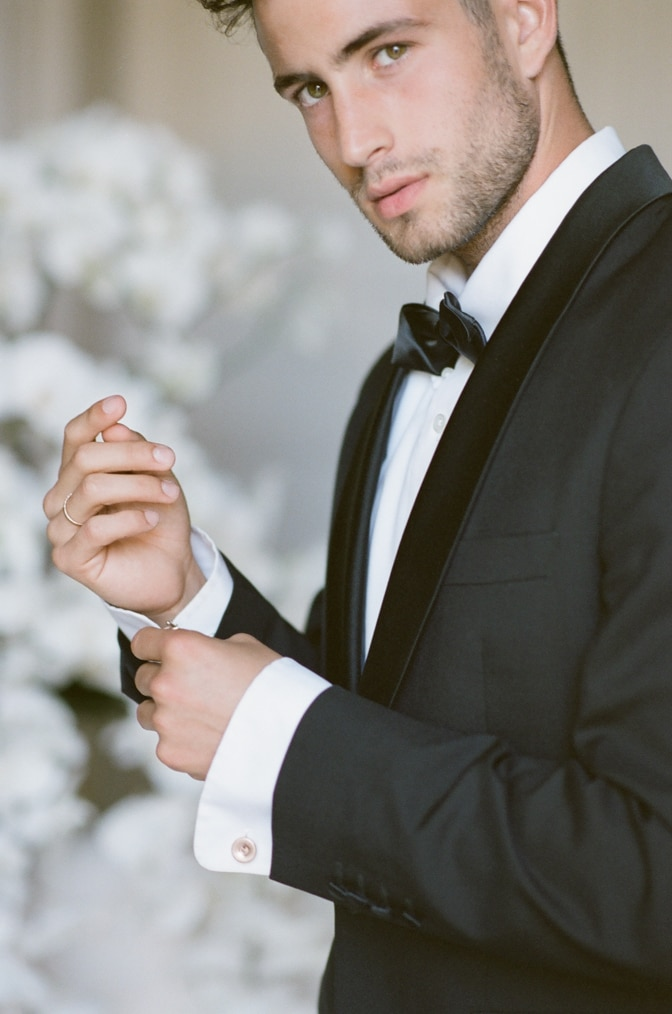 A styling guide for the modern groom showcasing a groom putting his cufflinks on