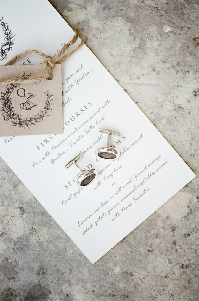 A styling guide for the modern groom showcasing black and silver cufflinks laid out on a wedding invitation