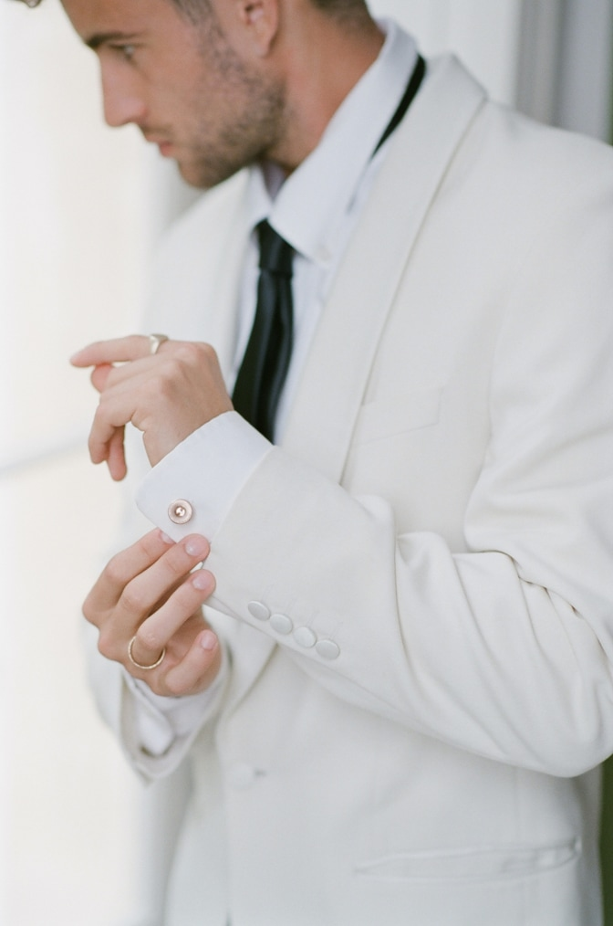 A styling guide for the modern groom showing a groom putting his gold cufflinks on