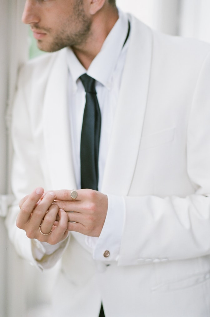 A styling guide for the modern groom showing groom's hands wearing gorgeous gold bands
