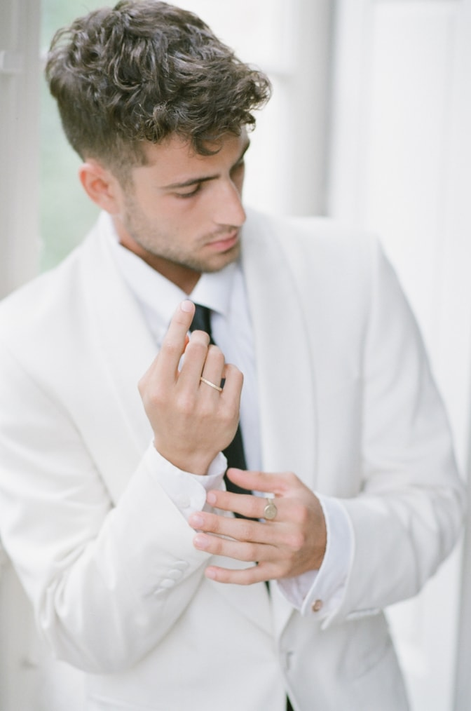 A styling guide for the modern groom showing a groom with his gold jewelry