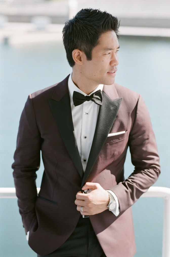 a style guide for the modern groom showing a groom in his burgundy colored jacket