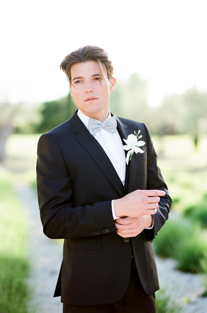 a style guide for the modern groom showing a groom in his black jacket with a blue bowtie