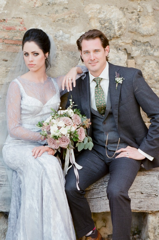 Bride and groom sitting on a bench at Borgo Pignano in Tuscany for luxury destination wedding photographer Tamara Gruner