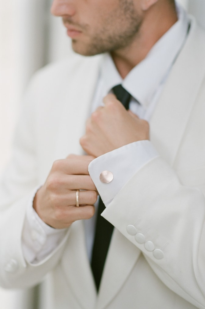 A style guide for the modern groom tying his black tie at the Chateau Martinay