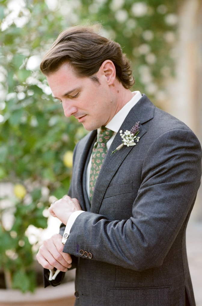 A style guide for the modern groom showing a groom in his grey suit and his green tie