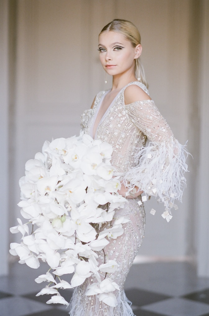 Bride wearing Ziad Nakad gown and holding an orchid bouquet