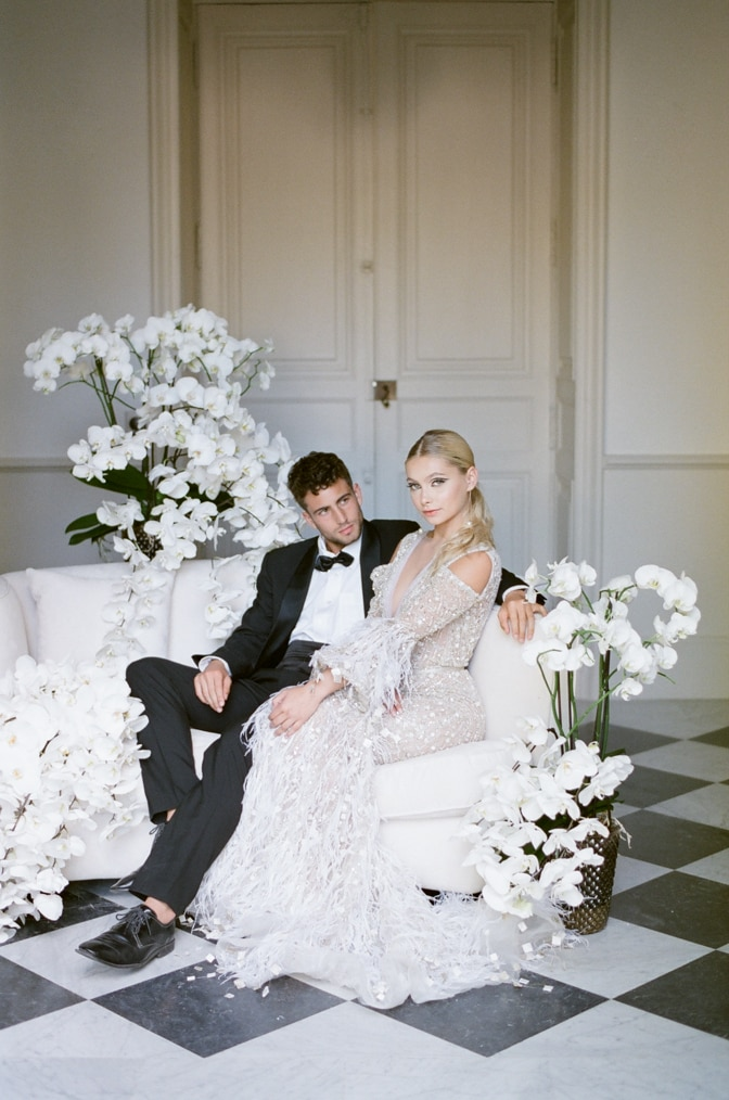 Bride and groom sitting together on a chaise at Chateau Martinay in Provence, France
