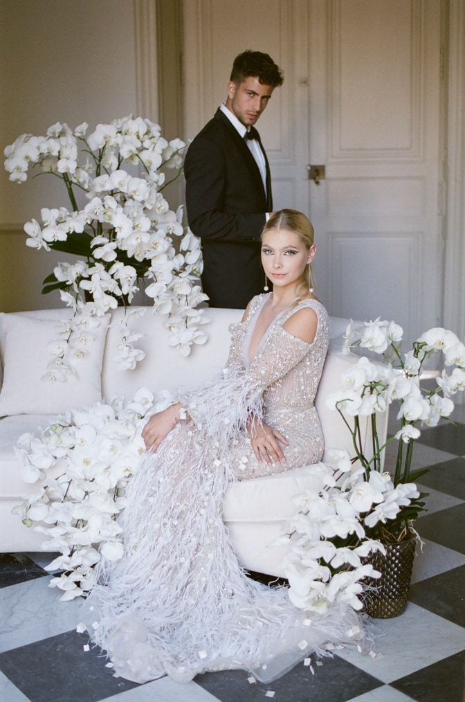 Bride sitting on a chaise with groom standing behind her during their French elopement