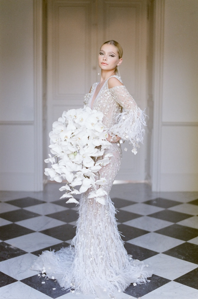 Ziad Nakad bride holding her huge orchid bouquet and posing in the hallway of Chateau Martinay for French Wedding Photographer Tamara Gruner
