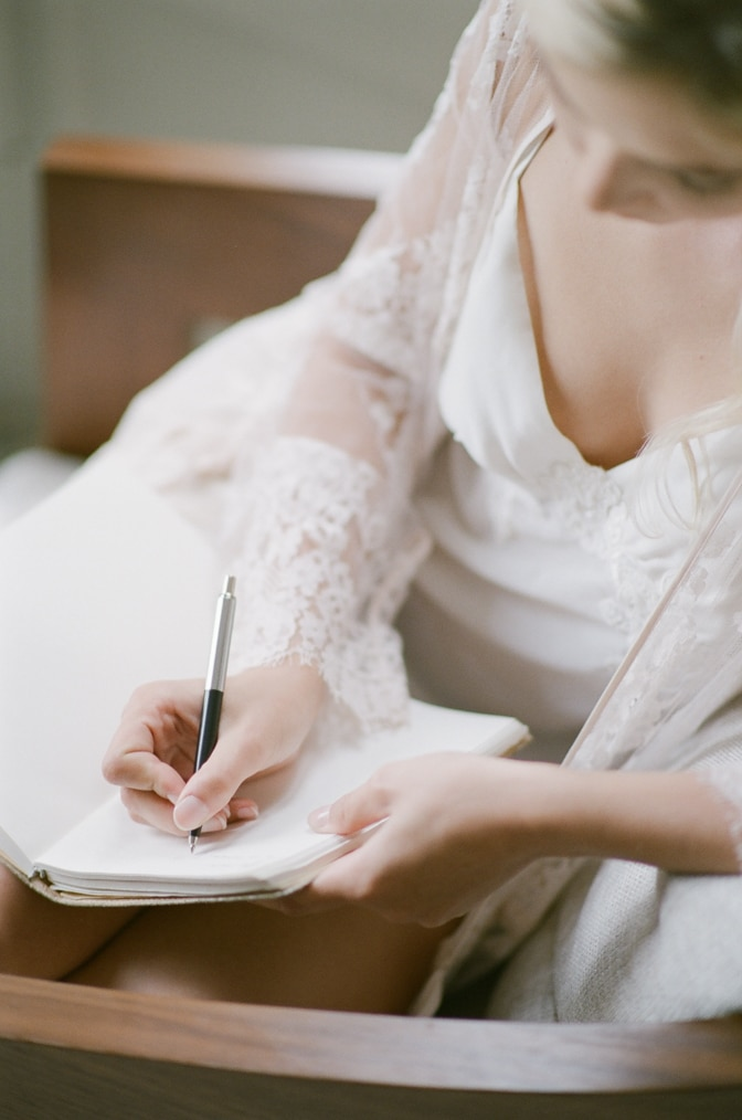 Closeup of bride writing into her journal before her French chateau rehearsal