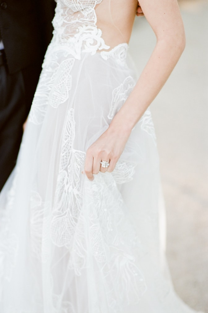 Closeup of a bride holding her wedding dress while wearing her luxury designer engagement ring by Susie Saltzman