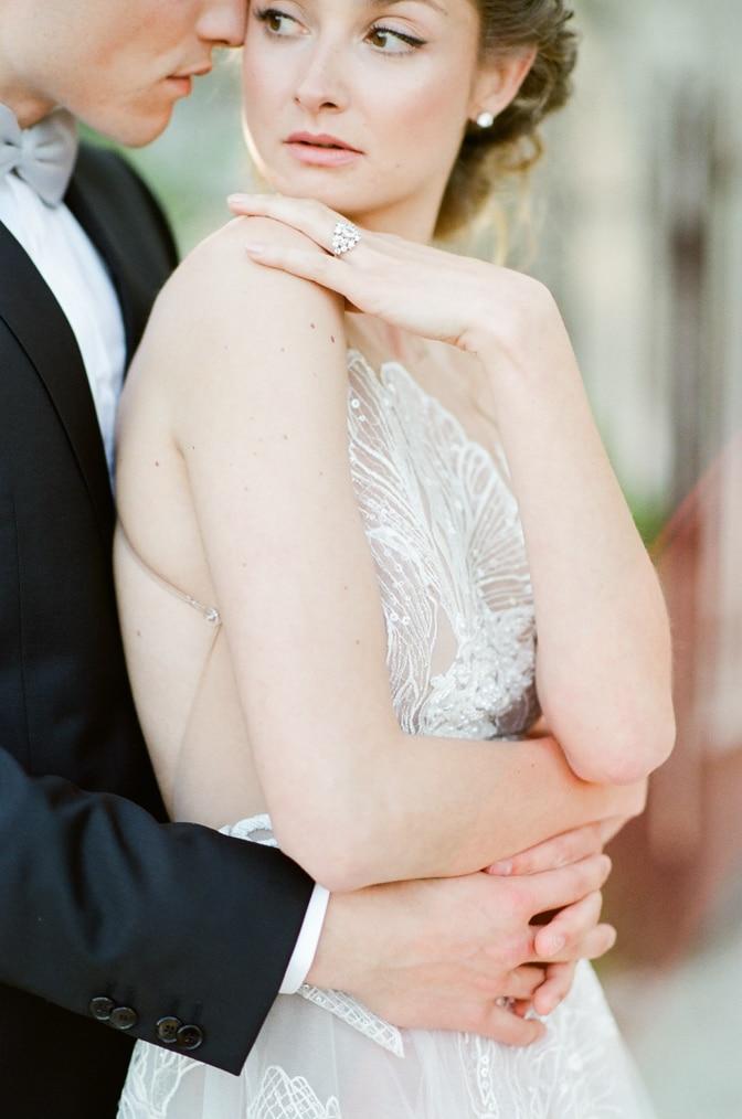 Groom embracing bride wearing a luxury designer engagement ring by Susie Saltzman