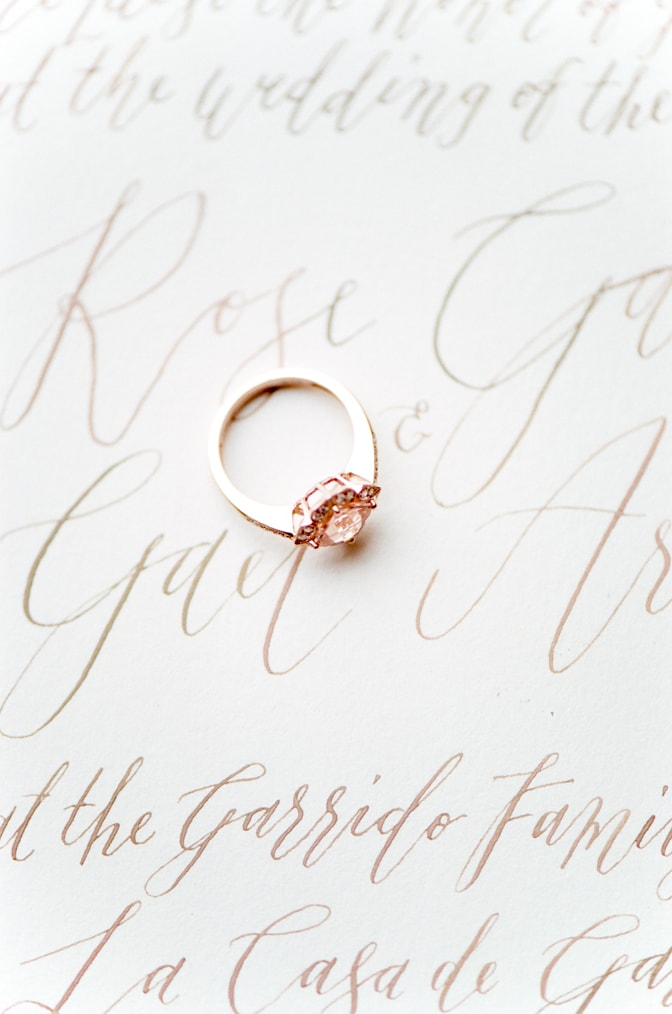 Closeup of a luxury designer engagement ring by Brian Gavin placed on an invitation suite