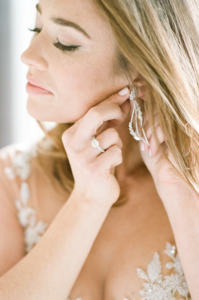 Closeup of a bride putting her earrings on while wearing a luxury expensive designer engagement ring by Tiffany & Co