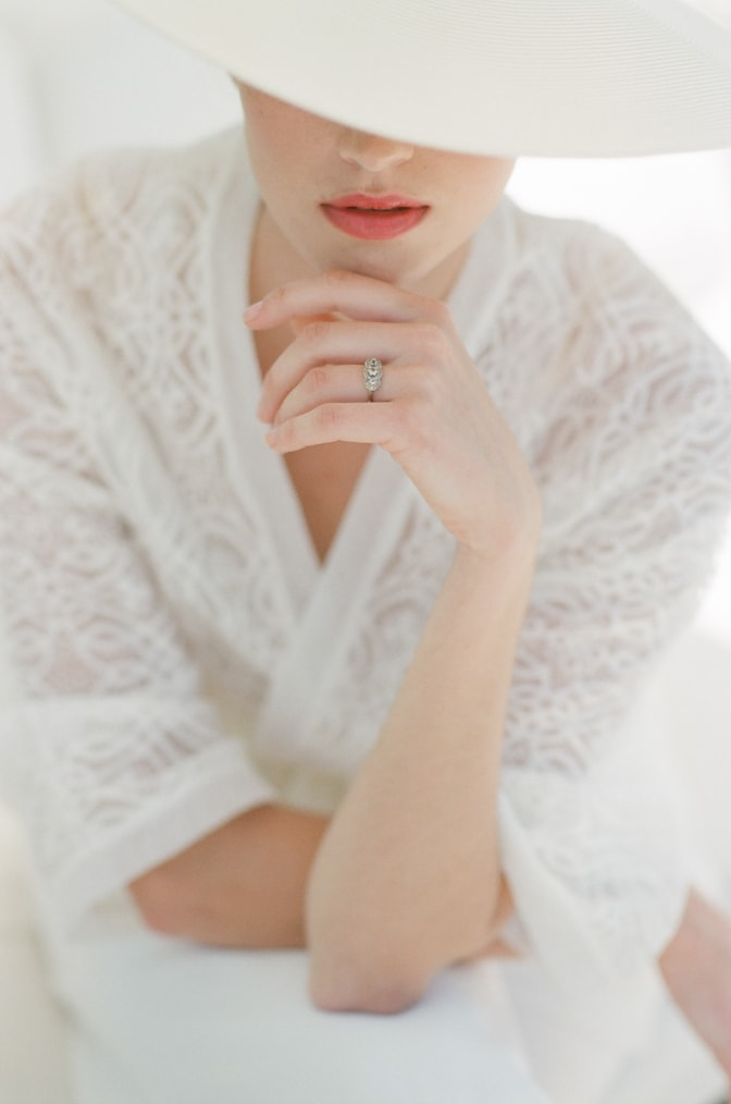Closeup of bride wearing a hat and showing her unique luxury designer engagement ring by Michaela Roemer