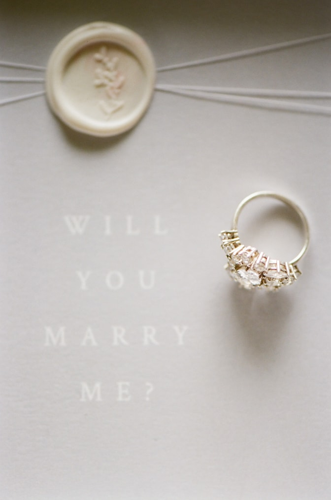 """Luxury designer engagement ring by Susie Saltzman placed on an invitation sign saying 'Will you marry me?"""""""