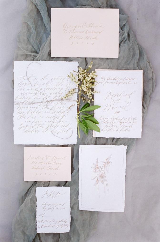 Flatlay of luxury romantic wedding invitation on blue silk