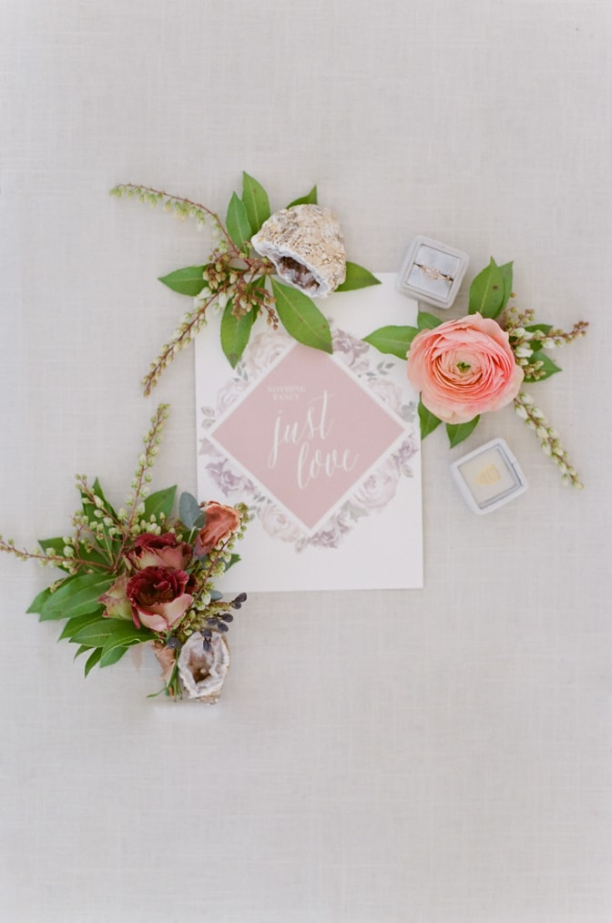 Closeup of luxury wedding invitation shown in blush and white