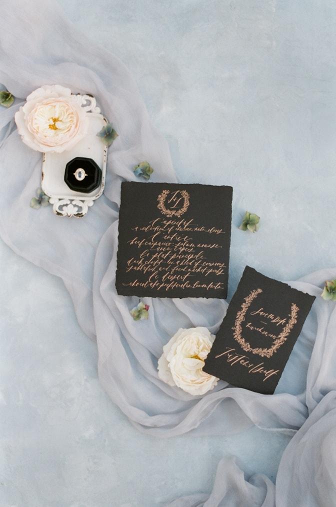 Flatlay of luxury handmade wedding invitation in black with copper calligraphy