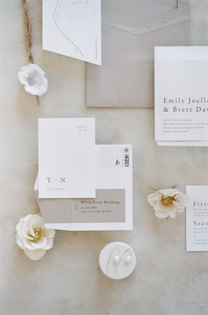 Closeup of modern luxury letterpress wedding invitation in white and beige