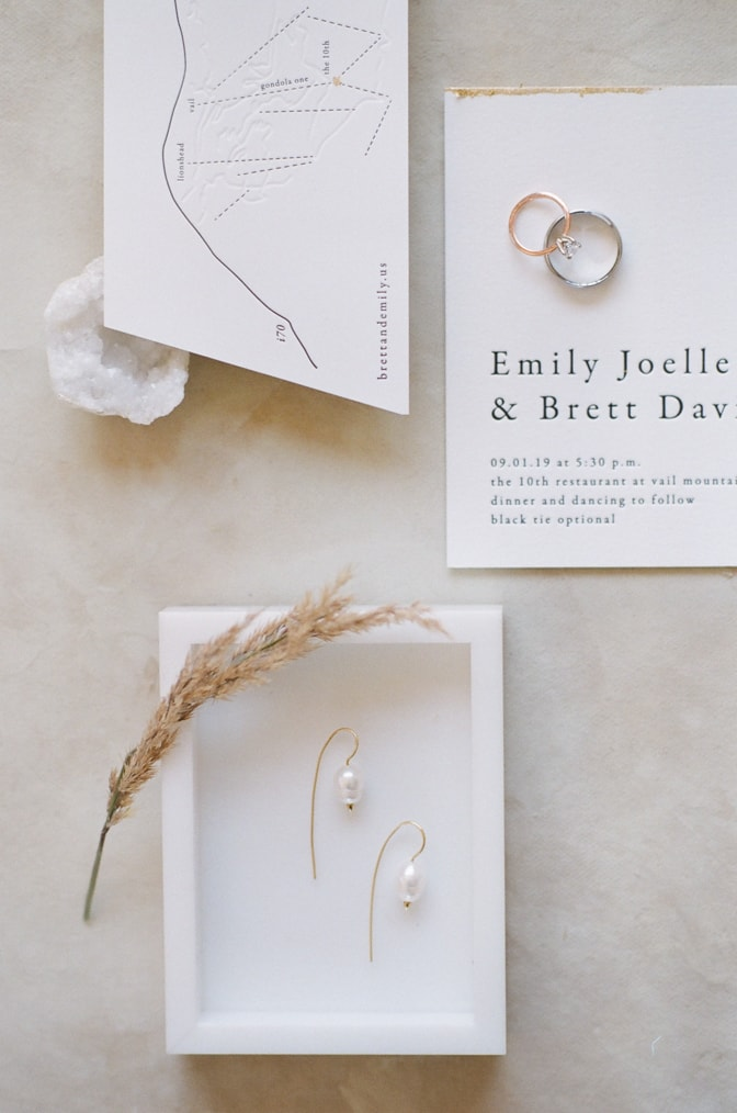 Closeup of modern luxury letterpress wedding invitation and earrings