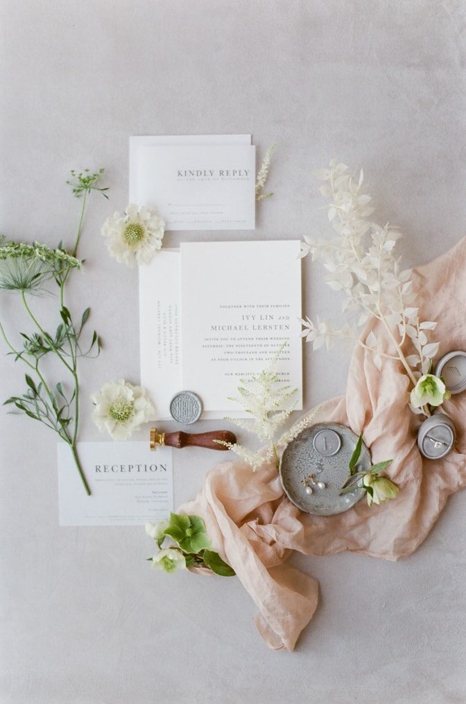 Modern luxury letterpress wedding invitation surrounded by florals