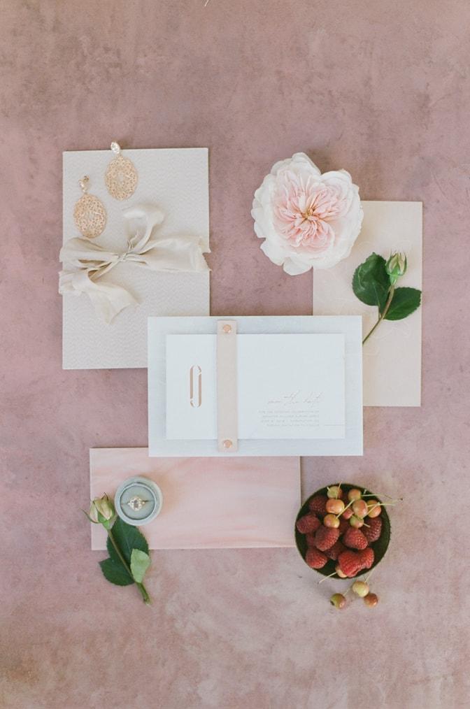 Flatlay of luxury acrylic wedding invitation on red backdrop