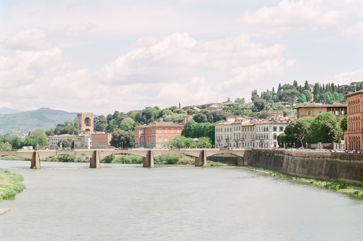 Beautiful bridge on the river Arno in Florence and soft buildings and greenery behind it