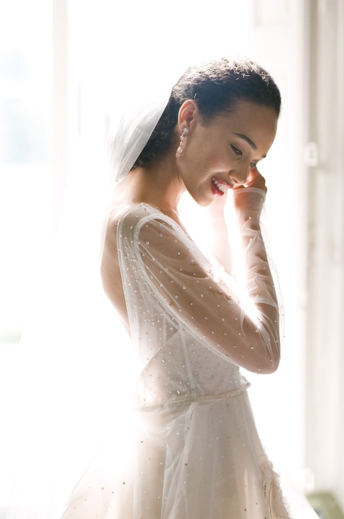 A black bride in her blush Inbal Dror wedding dress putting her earrings on at Chateau Martinay