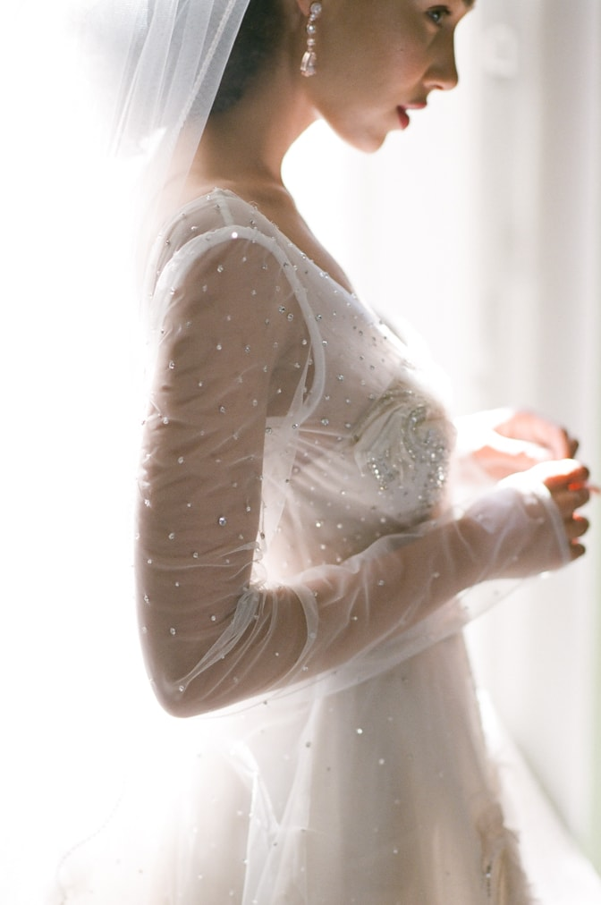 Closeup of a blush Inbal Dror wedding gown made out of sheer tulle and crystals