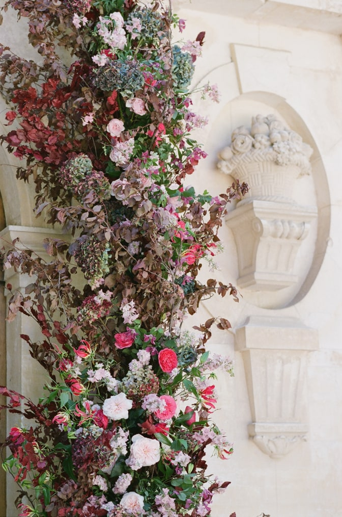 Closeup of a floral wedding arch in red, blush and pinks at Chateau Martinay in Provence