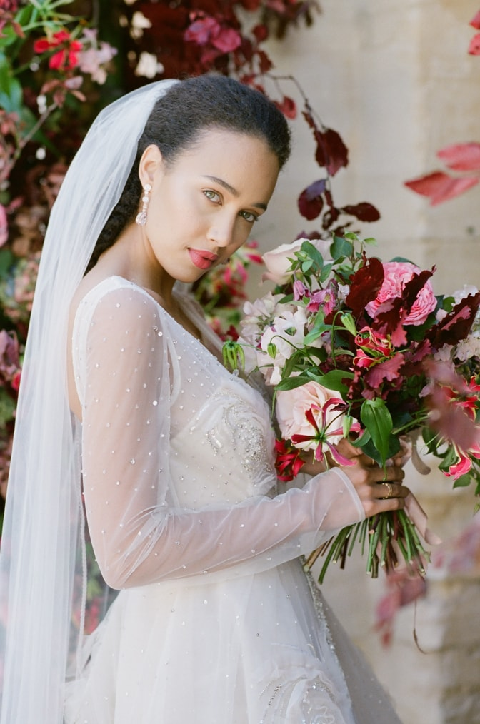 Closeup of a black bride in her blush Inbal Dror wedding gown holding her colorful bouquet at Chateau Martinay