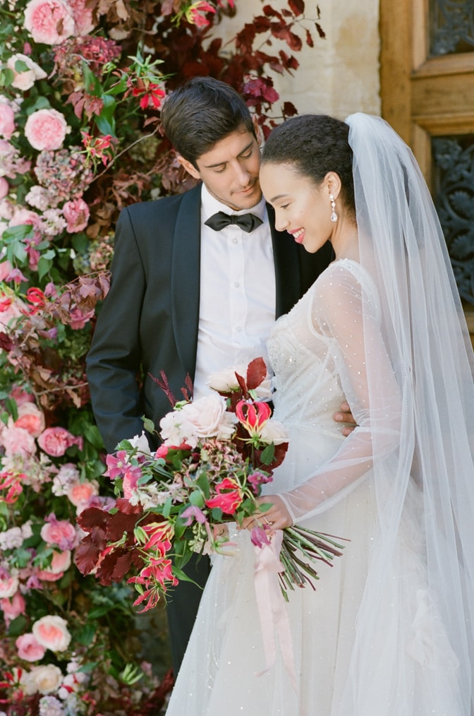 Bride and groom smiling under the wedding floral arch at Chateau Martinay in Provence