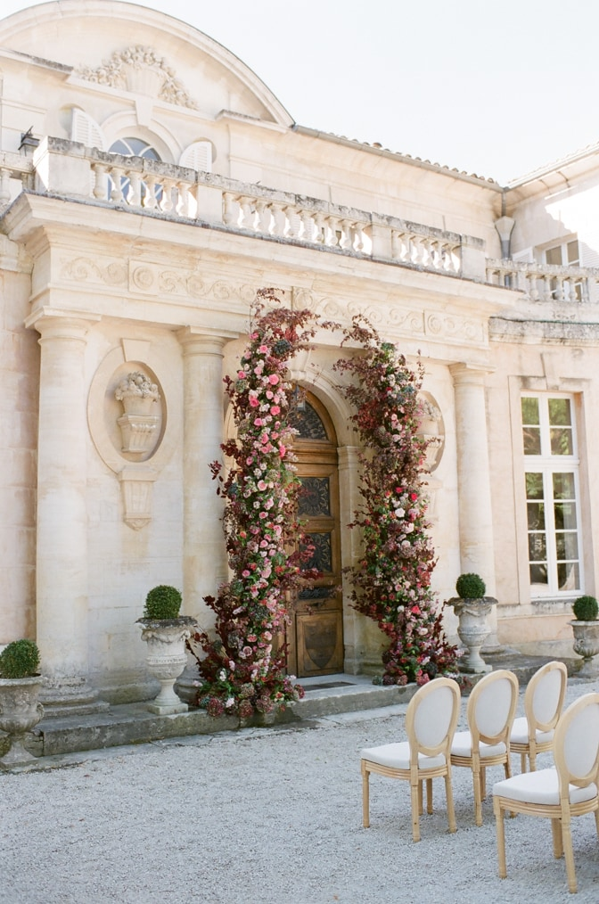 Ceremony floral arch in red, blush and pink at the entrance of Chateau Martinay in Provence