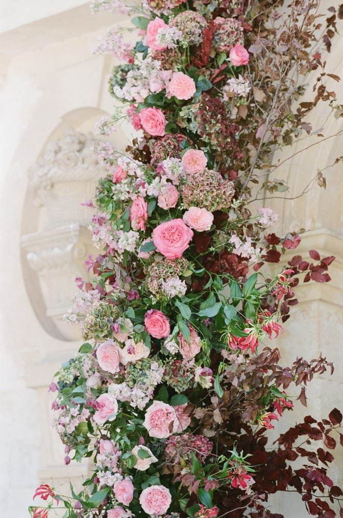 Closeup of a flower arch in red, blush and pink tones at Chateau Martinay in Provence