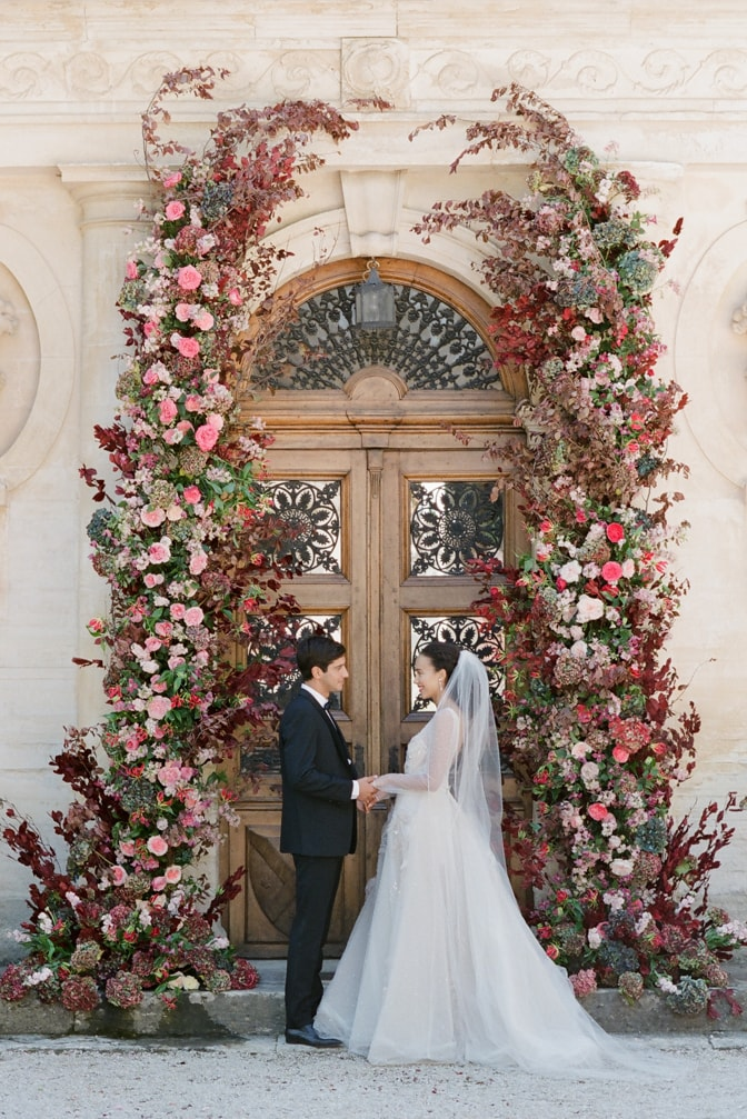 Bride and groom holding each others hands during their wedding ceremony at Chateau Martinay in Provence