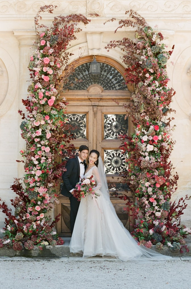 Bride and groom under the wedding ceremony arch smiling into the camera at Chateau Martinay in Provence