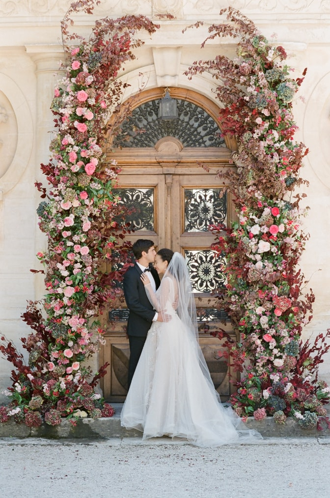 Groom kissing his bride under the ceremony arch at Chateau Martinay in Provence