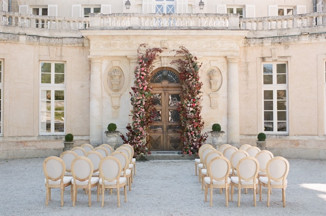 Flower wedding arch in red, blush and pinks adorning the entrance of Chateau Martinay in Provence