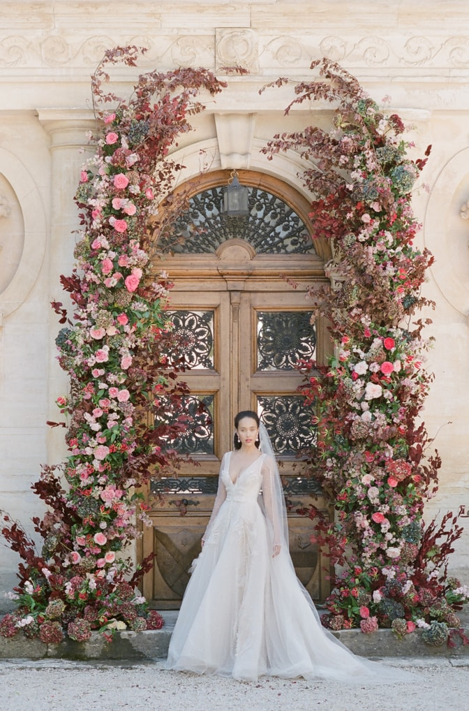 Bride standing at entrance of Chateau Martinay surrounded by her glamorous flower arch