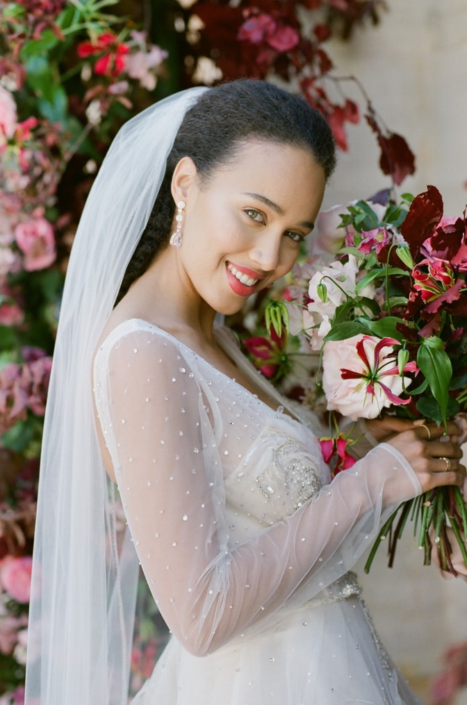 Bride holding her wedding bouquet and smiling into the camera at Chateau Martinay in Provence