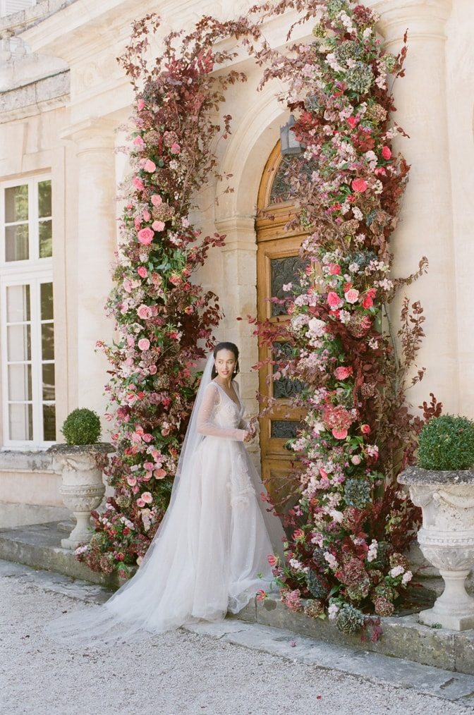 Bride standing under her flower wedding arch in front of Chateau Martinay in Provence